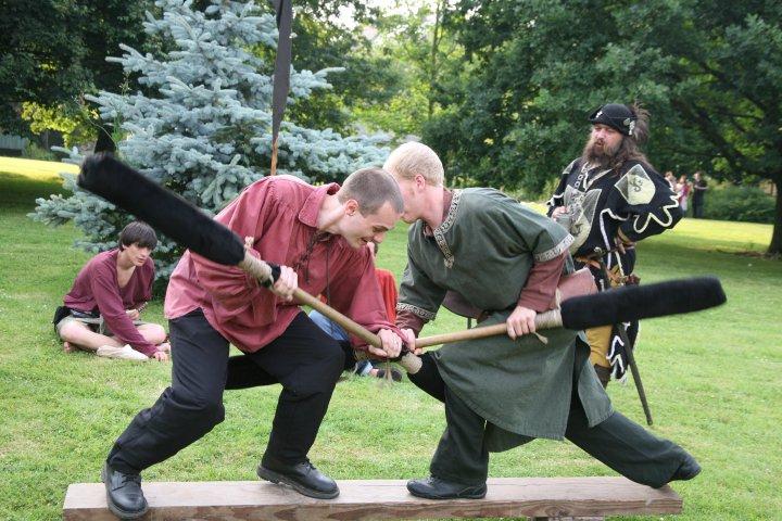L'équipe élira le meilleur duelliste par élimination. Le vainqueur se battra en duel contre l'animateur en trois manches gagnantes et recevra 6 écus. Les bâtons sont protégés par de la mousse et les duellistes sont en équilibre sur une planche à 20 cm du sol. Il ne s'agit en aucun cas de frapper l'adversaire mais de le pousser. Les animateurs sont là pour faire respecter la non-violence de l'épreuve. * The team will select the best dueller by elimination. The winner will duel against the instructor in three rounds and will receive 6 gold coins. The duellers use pugil sticks (padded poles) while balancing on a beam 20 cm from the ground. The aim is not to knock the opponent off, but to push him/her. The instructors' role is to see to it that the event remains non-violent.* Elk team kiest zijn beste duellist via eliminatie. De winnaar duelleert in drie rondes tegen de animator en kan 6 gouden munten in de wacht slepen. De stokken zijn met mousse beschermd en de duellisten moeten hun evenwicht bewaren op een balk 20 cm boven de grond. Het is niet de bedoeling om de tegenstander te slaan, maar wel om hem of haar ervan te duwen. De animatoren zien erop toe dat de proef geweldloos verloopt.